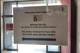 Hinweisschilder machen an geeigneten Stellen die neuen Inhaber eines Personalausweises auf das Terminal aufmerksam.