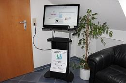 Foto: Die SID-Box an einem 27 Zoll Touchscreen. Der fahrbare Computertisch konnte bei Jago für 32,85 Euro erworben werden (www.jago24.de).