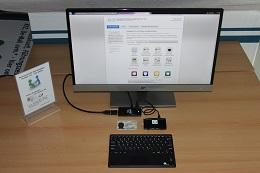 Foto: Die SID-Box kann an einem Intel Compute-Stick mit 2 GB Arbeitsspeicher betrieben werden. Der Compute-Stick wird dabei über HDMI an einem HD-Display angeschlossen. Die Tastatur mit integriertem Mauspad wird über Bluetooth gekoppelt. Auf der Arbeitsfläche ist neben dem Monitor nur noch die Tastatur und die SID-Box zu sehen. Der Compute-Stick verschwindet hinter dem Monitor.